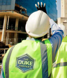 Construction Worker Wearing Safety Vest with Duke Company Logo